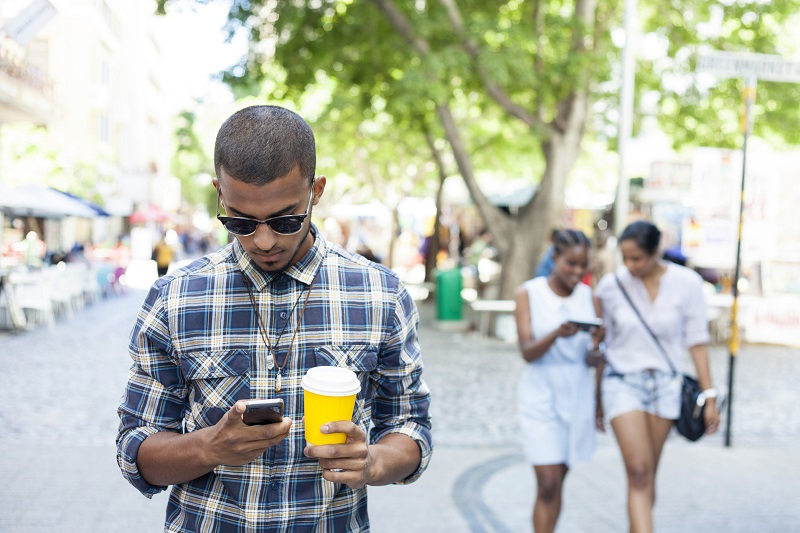 African male looking down at his phone in his right hand and holding coffee in his left had. He has sunglasses on his face. Cape Town, Western Cape, South Africa.